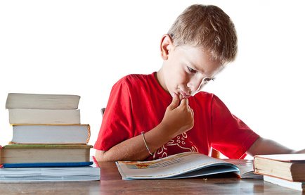 A little boy hard at work on his homework, getting ready to go back to school. Isolated on white background with plenty of copyspace.