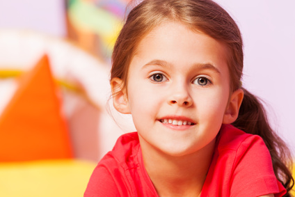 Close portrait of smiling little girl with subtle smile look at camera