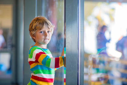Cute little tired kid boy at the airport, traveling. Upset child waiting near window and looking at plane. Canceled flight due to pilot strike.